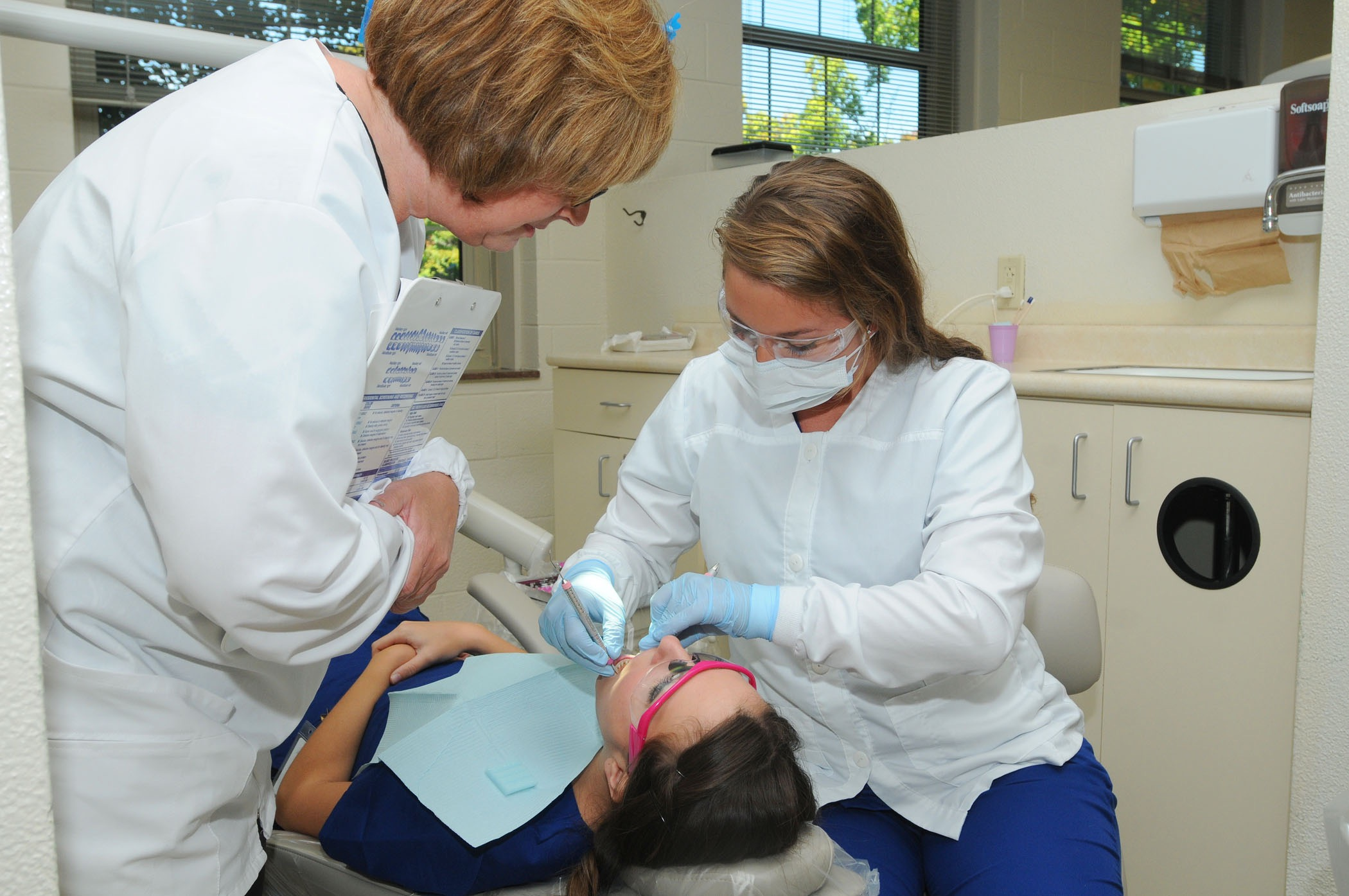 students with a patient in the dental hygiene clinic